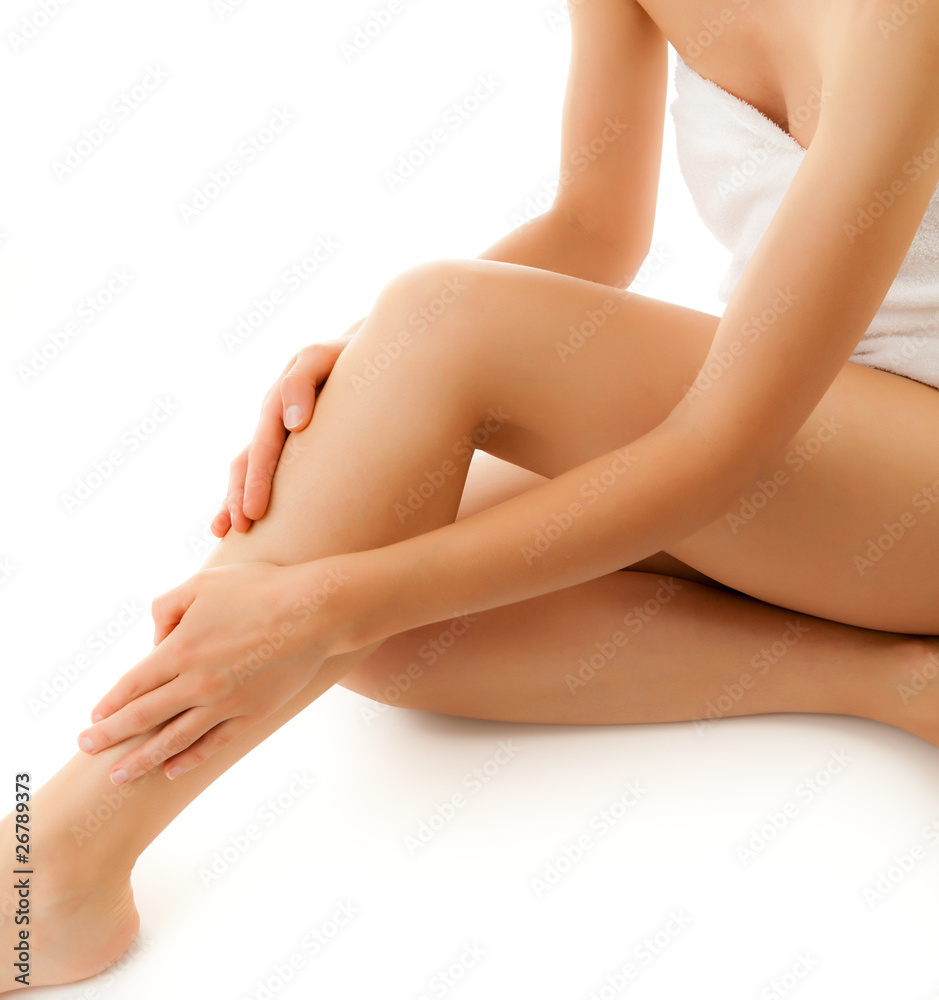 Fototapeta Woman massaging legs sitting on white background