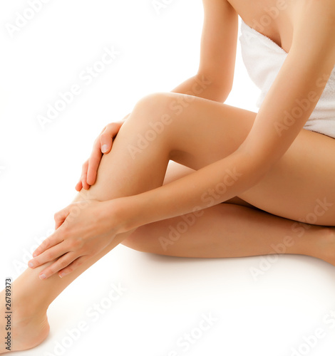 Fotografía  Woman massaging legs sitting on white background