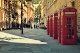 Fototapeta Londyn - Street with traditional red Phone Boxes, London.