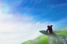 Surfer Hitting Wave Lip Against Beautiful Blue Skies