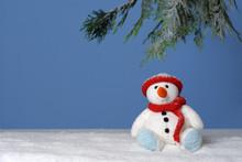 Cute Snowman Sitting Under A Pine