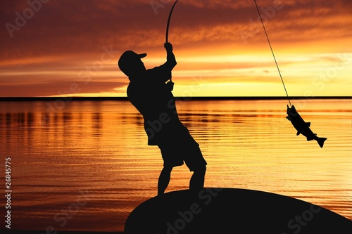 Fotobehang Vissen fisherman with a catching fish on sunrise background