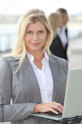Fototapety, obrazy: Blond businesswoman with laptop computer