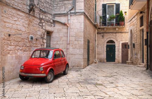 Fototapeta na wymiar Czerwony mały samochód we włoskiej uliczce