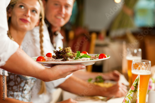 Fotografie, Obraz  Kellnerin serviert in bayerischem Restaurant