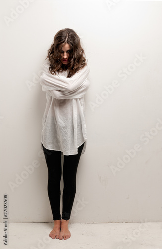 Fotografia Young insane woman with straitjacket standing looking at camera