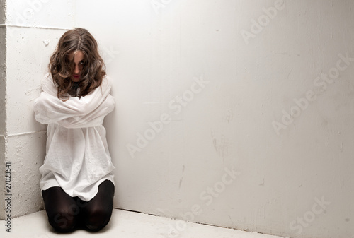 Fotografia Young insane woman with straitjacket on knees looking at camera