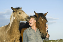 Happy Laughing Man Petting His Horse And Foal