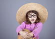 Funny girl in cap and glasses keeping pumpkin.