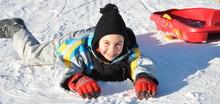 Sport D'hiver Fillette Joyeuse Couché Sur La Neige Avec Sa Luge