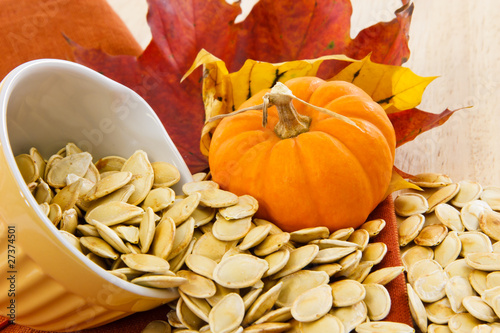 Fotografie, Obraz  Toasted pumpkin seeds spilling from a yellow bowl