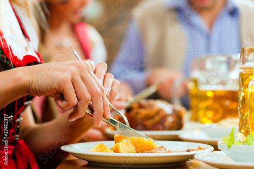 Fototapeta Leute essen Schweinebraten in Restaurant obraz