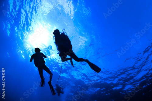 Fotobehang Duiken Scuba Divers in silhouet with sunburst on blue background
