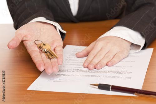 Fotografía  Frau übergibt Schlüssel und Mietvertrag am Schreibtisch