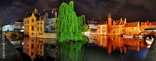 Panorama of old buildings and canal in th night Brugge