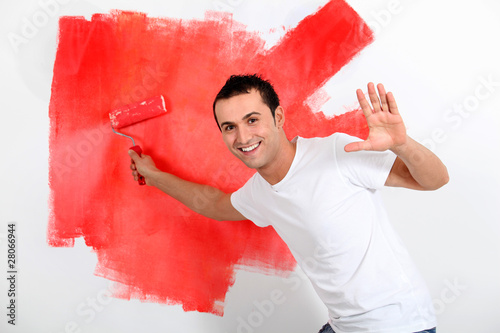 Young man painting house wall in red - Buy this stock photo and