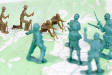 Plastic Army Men Fighting On Topographic Map Opposing Sides War