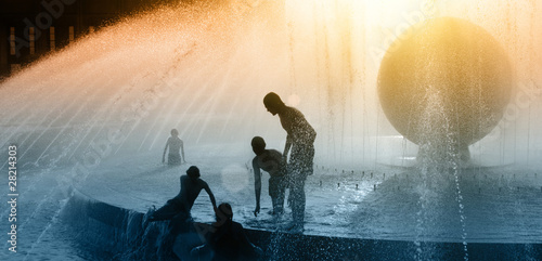 Children silhouettes playing in water fountain at sunset Fototapet