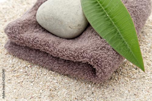 Photo sur Plexiglas Zen pierres a sable serviette, galet et feuille de frangipanier sur sable blanc
