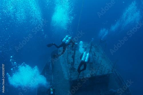 Poster Naufrage Scuba divers descending on a shipwreck.