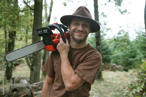 Photo sur Aluminium Noir bûcheron et sa tronçonneuse en forêt