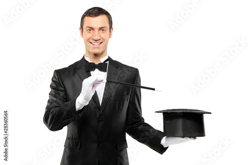 Magician in a black suit holding an empty top hat and magic wand