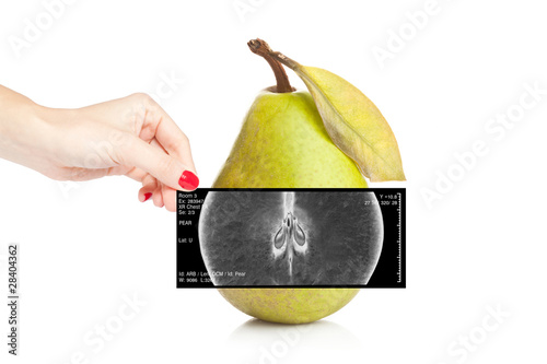 Fotografie, Obraz  Female doctor holding an x-ray revealing inner view of a pear