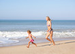 Mother chasing young girl on beach
