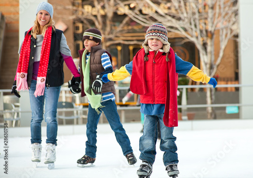 Fotobehang Wintersporten a family skates together at an ice rink