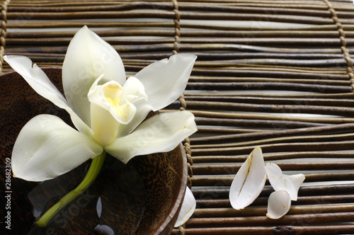 In de dag Spa bowl of orchid, petal on bamboo mat