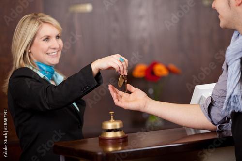 Foto rezeptionistin überreicht zimmerschlüssel
