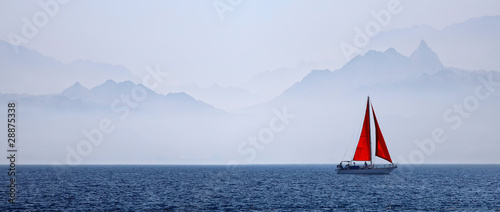 Fotografia Yacht with a red sail on a mountain background