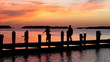 Family Silhouetted On Dock