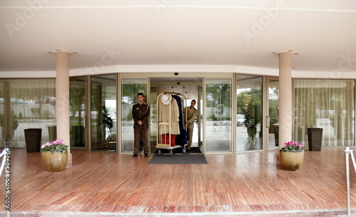 Fotografie, Obraz  Bellboy delivering luggage to hotel with doorman standing by