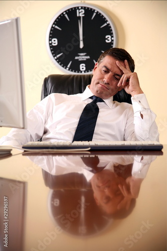 Businessman sitting at his desk lost in thought Poster