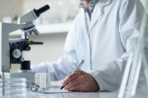 scientist conducting research with microscope Fototapeta