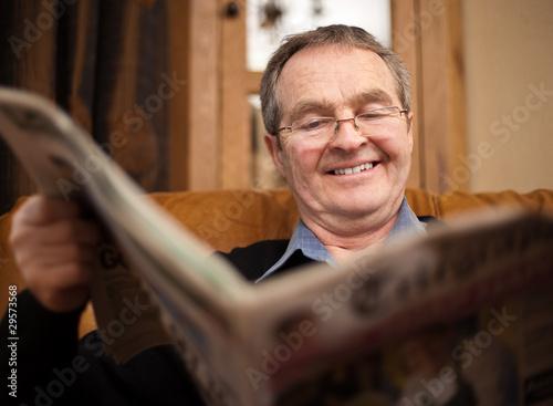 Fototapeta Old man happy reading newspaper obraz na płótnie