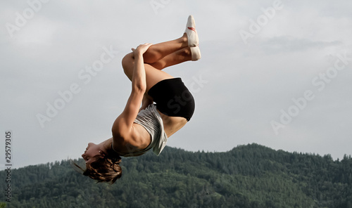 female gymnast doing back somersault in nature