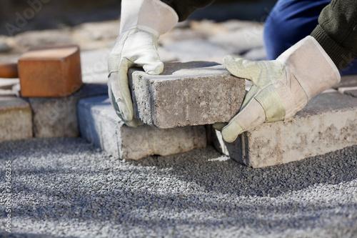 Poster Taupe handwerker verlegt steine auf dem hof