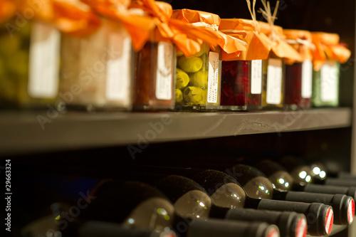 Fotografía  Weinflaschen und Einweckgläser in einem Regal