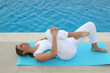 Woman doing exercises by a swimming-pool