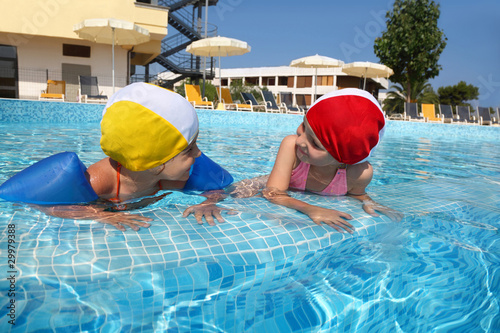 Photo  Two girls bath in  pool near skirting in  day-time on rest