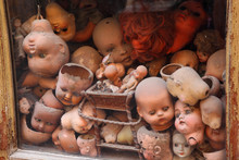 Old Showcase With Many Old Heads Dolls, Red Doll Hair