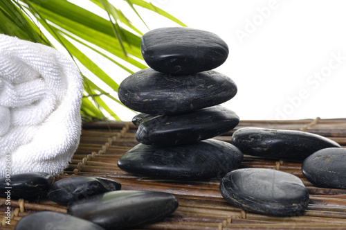 Poster Spa Spa setting with white towel, pebbles, with palm leaf