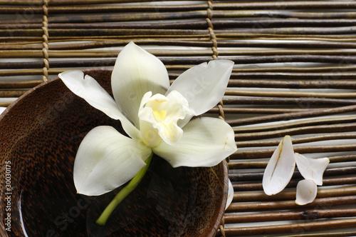 Fotobehang Spa Wooden bowl of orchid, petal on bamboo mat