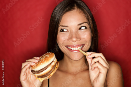 Fotobehang Kruidenierswinkel Junk food woman eating burger