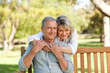 canvas print picture - Senior woman hugging her husband who is on the bench