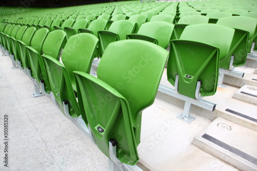Foto op Plexiglas Stadion Rows of folded, green, plastic seats in very big, empty stadium.