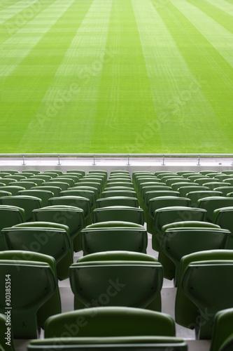 Foto op Plexiglas Stadion Rows of folded, green, plastic seats in very big, empty stadium