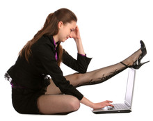 Girl In Black Suit Sits On Floor And Put Leg On Notebook.